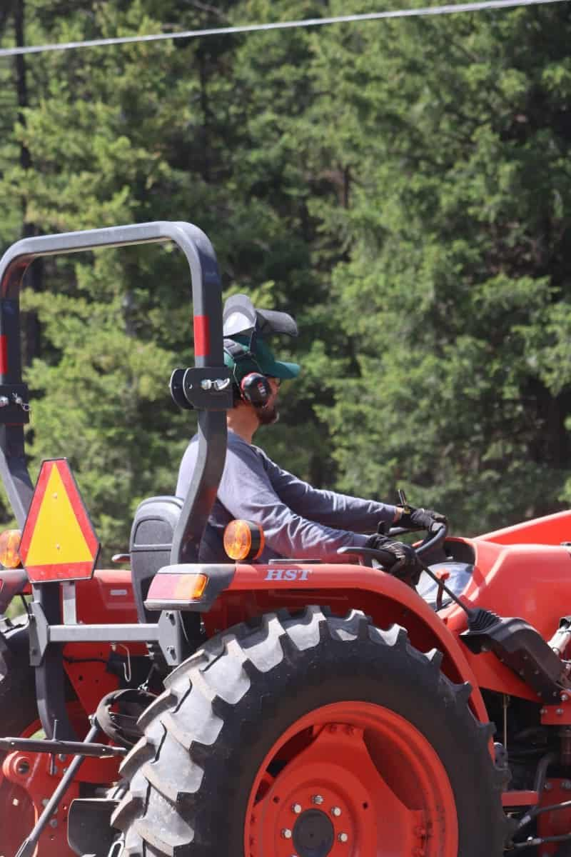 Man driving a orange tractor